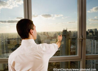 Picture of a young adult businessman standing in front of windows in a high rise holding a pen out in front of him at arms reach.  The man is sighting in on something with his pen.